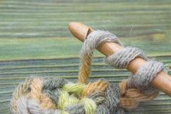 A foto do close up de faz crochê a corrente Rústico fazer crochê a linha e um gancho de bambu Aqueça a bola verde do fio do inver Imagens de Stock