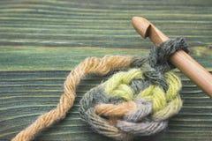 A foto do close up de faz crochê o doily Rústico fazer crochê a linha e um gancho de bambu Aqueça o fio verde do inverno para faz Imagem de Stock Royalty Free