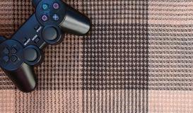 Foto do close-up de um controlador sem fio plástico preto do jogo em um fundo da tampa de tela quadriculado Manche do jogo Deixe  foto de stock royalty free