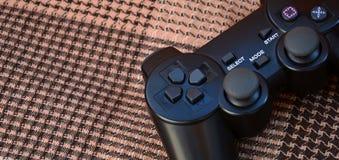 Foto do close-up de um controlador sem fio plástico preto do jogo em um fundo da tampa de tela quadriculado Manche do jogo Deixe  foto de stock