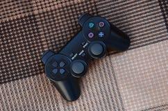 Foto do close-up de um controlador sem fio plástico preto do jogo em um fundo da tampa de tela quadriculado Manche do jogo Deixe  imagem de stock