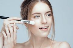 Foto do close-up de uma menina bonita com uma escova da composição Tem limpo e mesmo a pele, cabelo justo fotos de stock