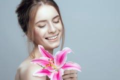 Foto do close-up de uma menina bonita com uma flor do lírio Tem limpo e mesmo a pele, cabelo justo foto de stock royalty free