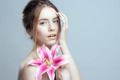 Foto do close-up de uma menina bonita com uma flor do lírio Tem limpo e mesmo a pele, cabelo justo fotografia de stock royalty free