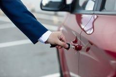 Foto do close up do homem na porta de carro da abertura do terno com chave Foto de Stock