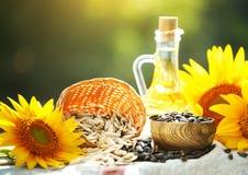Foto do close up dos girassóis e do óleo de girassol com sementes sobre em uma tabela de madeira Bio e conceito orgânico do produ Fotos de Stock
