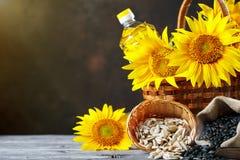 Foto do close up dos girassóis e do óleo de girassol com sementes sobre em uma tabela de madeira Bio e conceito orgânico do produ Imagem de Stock
