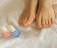 Foto do close up dos pés da mulher em uma toalha branca com garrafas do verniz para as unhas foto de stock