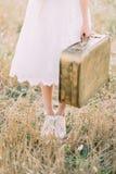 A foto do close-up dos pés da noiva vestiu-se no vestido até o joelho e em levar a mala de viagem do vintage no Foto de Stock