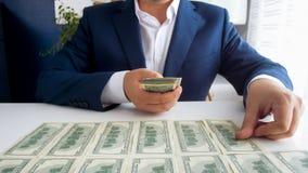 Foto do close up do homem de negócios bem sucedido que coloca o dinheiro na frente dele na mesa de escritório imagem de stock royalty free