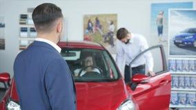 Foto do consultante masculino novo e compradores na feira automóvel Consultante que mostra o polegar acima e o sorriso Conceito p filme