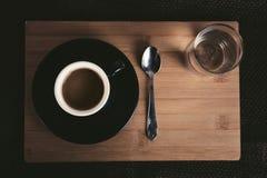 Foto do copo de café preto pequeno iluminado na tabela de madeira com a colher e o vidro do chá completos da água clara no fundo  foto de stock royalty free
