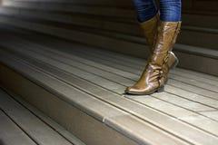 Foto do ` de couro s da mulher com as botas na fuga de madeira Fotos de Stock