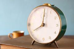 Foto do despertador velho sobre a tabela de madeira, com efeito retro desvanecido Fotos de Stock