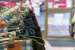 Foto do detalhe - calças e calças de brim em ganchos na loja de parcimônia da caridade foto de stock