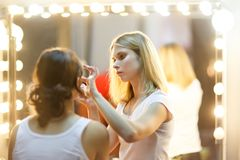 Foto do estilista com a menina na frente do espelho com luzes imagens de stock royalty free