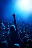A foto do estilo do Grunge, mãos dos povos aumentou acima no concerto musical Fotos de Stock Royalty Free