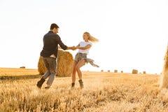 Foto do homem alegre e da mulher dos pares que têm o divertimento ao andar o th fotos de stock