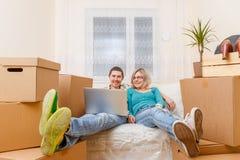 Foto do homem com o portátil e a mulher que sentam-se no sofá entre caixas de cartão fotografia de stock