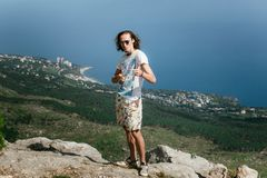 Foto do homem engraçado considerável novo que está sobre montanhas e que olha a câmera foto de stock