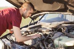 A foto do homem está na frente da capa aberta do carro, tem brocken o veículo na estrada, tenta resolver o problema e reparar o d imagens de stock royalty free