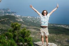 Foto do homem feliz considerável novo que está sobre montanhas e que olha a câmera fotografia de stock