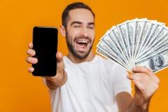 Foto do homem feliz 30s no telefone celular da terra arrendada do vestuário desportivo e no fã do dinheiro, isolados sobre o fund fotografia de stock royalty free