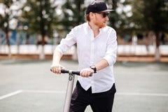 Foto do homem moderno com o 'trotinette' elétrico na rua imagem de stock royalty free
