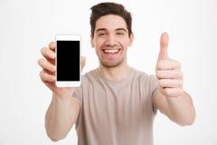 Foto do homem no t-shirt bege que demonstra o scre preto do copyspace fotografia de stock