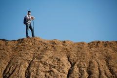 Foto do homem novo do turista com as varas para andar no monte contra o céu azul imagem de stock royalty free