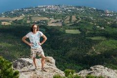 Foto do homem sério considerável novo que está sobre montanhas e que olha a câmera fotografia de stock royalty free