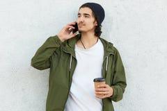 A foto do indivíduo não barbeado sério bebe o coffe afastado, tem a conversação telefônica, vestida pensativamente de lado no equ fotos de stock royalty free