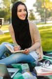 Foto do lenço vestindo da mulher árabe atrativa que escreve para baixo notas no caderno fotos de stock royalty free