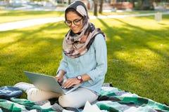 Foto do lenço vestindo fêmea muçulmano do estudante 20s que senta-se na cobertura no parque verde fotos de stock