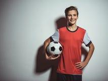Foto do menino adolescente no sportswear que guarda a bola de futebol imagem de stock royalty free
