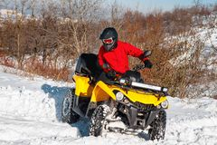 Foto do motorista extremal novo na roupa morna vermelha do inverno e no salto preto do capacete no ar com a bicicleta do quadrilá imagem de stock royalty free