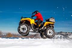 Foto do motorista extremal novo na roupa morna vermelha do inverno e no salto preto do capacete no ar com a bicicleta do quadrilá imagem de stock