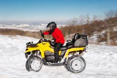 A foto do motorista extremal novo na roupa morna vermelha do inverno e o capacete preto conduzem seu suporte da bicicleta do quad imagens de stock