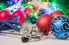 Foto do Natal médico e do ano novo - o estetoscópio ou o phonendoscope são ficados situado perto das bolas para a árvore de Natal Imagem de Stock Royalty Free