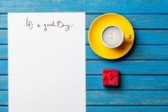Foto do papel ele ` s um bom dia, uma xícara de café e um presente bonito em t Imagem de Stock