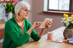 Foto do perfil da mulher idosa atrativa que toca na foto no quadro fotos de stock
