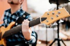 Foto do playng do músico em seis guitarras-baixo fretless da corda na rua na frente dos povos imagens de stock royalty free