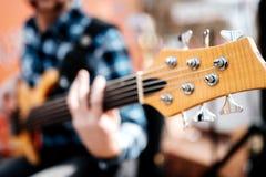 Foto do playng do músico em seis guitarras-baixo fretless da corda na rua na frente dos povos fotografia de stock