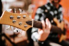 Foto do playng do m?sico em seis guitarras-baixo fretless da corda na rua na frente dos povos foto de stock royalty free