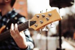 Foto do playng do m?sico em seis guitarras-baixo fretless da corda na rua na frente dos povos imagens de stock royalty free
