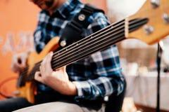 Foto do playng do m?sico em seis guitarras-baixo fretless da corda na rua na frente dos povos imagens de stock