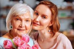 Foto do retrato da filha madura que abraça a mãe cinzento-de cabelo que guarda tulipas imagens de stock