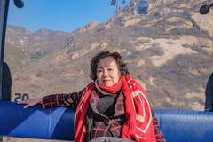 Foto do retrato do viajante asiático superior das mulheres que senta-se no teleférico para cruzar a montanha ao Grande Muralha de foto de stock royalty free
