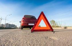 Foto do sinal vermelho do triângulo na estrada ao lado de carro quebrado Imagens de Stock Royalty Free