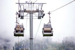 Foto do teleférico nas montanhas contra o fundo do céu enevoado imagem de stock